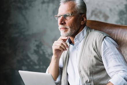 Homem mais velho pensativo em frente ao computador planejando a aposentadoria